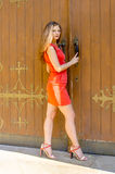 Красивая молодая женщина в красной прогулке краткости платья коктеиля от старого дома стоковые фотографии rf