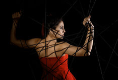 Красивая молодая женщина в красном платье спутанном в паутине веревочки на черной предпосылке Стоковые Фотографии RF