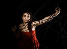 Красивая молодая женщина в красном платье спутанном в паутине веревочки на черной предпосылке Стоковое Изображение