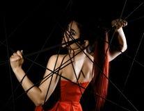 Красивая молодая женщина в красном платье спутанном в паутине веревочки на черной предпосылке Стоковые Изображения