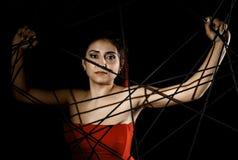 Красивая молодая женщина в красном платье спутанном в паутине веревочки на черной предпосылке Стоковое фото RF