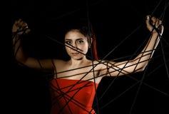 Красивая молодая женщина в красном платье спутанном в паутине веревочки на черной предпосылке Стоковая Фотография RF