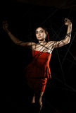 Красивая молодая женщина в красном платье спутанном в паутине веревочки на черной предпосылке Стоковая Фотография