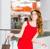 Красивая молодая женщина в красном платье с хозяйственными сумками в моле Стоковая Фотография RF