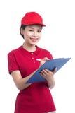 Красивая молодая женщина в красных футболке и крышке усмехаясь, h поставки Стоковая Фотография RF