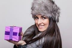 Красивая молодая женщина в меховой шапке держа настоящий момент Стоковое Изображение RF
