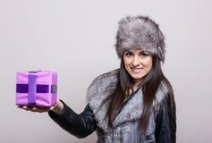 Красивая молодая женщина в меховой шапке держа настоящий момент Стоковое Фото