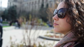 Красивая молодая женщина в солнечных очках в городе акции видеоматериалы