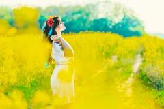 Красивая молодая женщина в украинце вышила положению в поле желтых цветков рапса стоковые фотографии rf