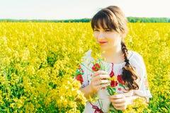 Красивая молодая женщина в украинце вышила положению в поле желтых цветков рапса Стоковые Изображения RF