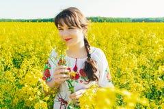Красивая молодая женщина в украинце вышила положению в поле желтых цветков рапса Стоковые Фото
