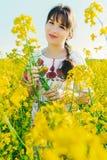 Красивая молодая женщина в украинце вышила положению в поле желтых цветков рапса Стоковое фото RF