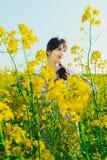 Красивая молодая женщина в украинце вышила положению в поле желтых цветков рапса Стоковая Фотография