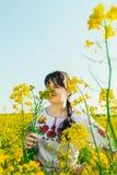 Красивая молодая женщина в украинце вышила положению в поле желтых цветков рапса Стоковое Изображение RF