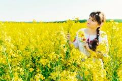 Красивая молодая женщина в украинце вышила положению в поле желтых цветков рапса Стоковое Изображение