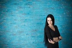 Красивая молодая женщина в черном платье представляя против фона голубой кирпичной стены Стоковая Фотография