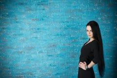 Красивая молодая женщина в черном платье представляя против фона голубой кирпичной стены Стоковое фото RF