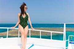 Красивая молодая женщина в черно-зеленом купальнике стоя на de Стоковые Фото