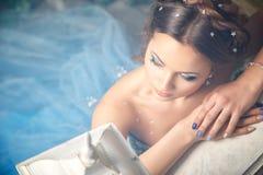 Красивая молодая женщина в шикарном голубом длинном платье как Золушка с совершенными составом и прической стоковые изображения
