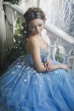 Красивая молодая женщина в шикарном голубом длинном платье как Золушка с совершенными составом и прической стоковое фото rf