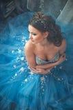 Красивая молодая женщина в шикарном голубом длинном платье как Золушка с совершенными составом и прической стоковые фотографии rf