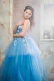 Красивая молодая женщина в шикарном голубом длинном платье как Золушка с совершенными составом и прической стоковые изображения rf