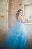 Красивая молодая женщина в шикарном голубом длинном платье как Золушка с совершенными составом и прической Стоковое Фото