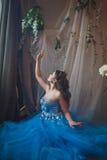 Красивая молодая женщина в шикарном голубом длинном платье как Золушка с совершенными составом и прической стоковая фотография rf