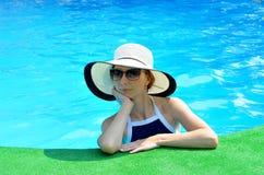 Красивая молодая женщина в шляпе и солнечных очках солнца на крае poo Стоковые Фото