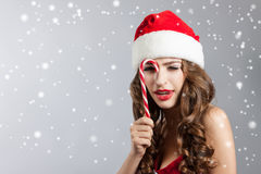 Красивая молодая женщина в шляпе Санта Клауса Портрет рождества девушки с конфетой солодки Стоковое фото RF
