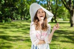 Красивая молодая женщина в шляпе смеясь над на парке Стоковое Изображение RF