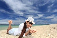 Красивая молодая женщина лежит на пляже Стоковые Изображения RF