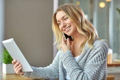 Красивая молодая женщина держа компьтер-книжку и говоря на телефоне на кафе Стоковое фото RF