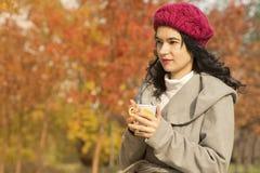 Красивая молодая женщина держа кружку в парке стоковые изображения rf