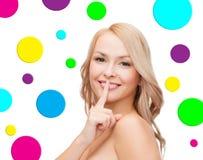 Красивая молодая женщина держа палец на губах Стоковые Фото