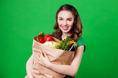 Красивая молодая женщина держа продуктовую сумку полный стоковые изображения
