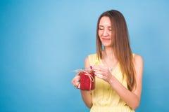 Красивая молодая женщина держа smoothie клубники на голубой предпосылке Здоровая органическая концепция пить Люди на диете Стоковая Фотография