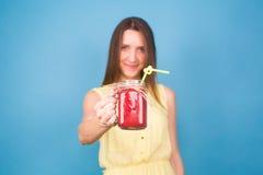 Красивая молодая женщина держа smoothie клубники на голубой предпосылке Здоровая органическая концепция пить Люди на диете Стоковые Фото