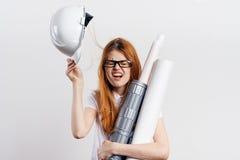 Красивая молодая женщина держит трудную шляпу и светокопии на светлой предпосылке, инженерстве, конструкции, эмоциях Стоковая Фотография