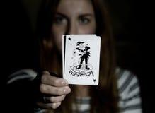 Красивая молодая женщина держит шутника играя карточки стоковые изображения