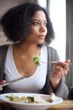 Красивая молодая женщина есть салат на ресторане Стоковое Фото