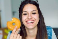 Красивая молодая женщина есть donuts дома Стоковые Фото