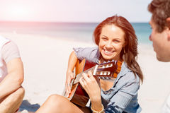 Красивая молодая женщина играя гитару на пляже Стоковое Изображение