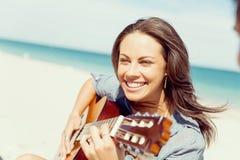Красивая молодая женщина играя гитару на пляже Стоковые Фото