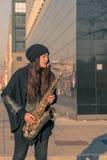Красивая молодая женщина играя саксофон тенора Стоковое Изображение