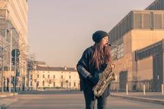 Красивая молодая женщина играя саксофон тенора Стоковые Изображения