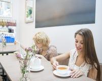 Красивая молодая женщина имея кофе в кафе Стоковая Фотография