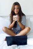 Красивая молодая женщина используя ее кофе amb компьтер-книжки выпивая на ho Стоковые Изображения RF