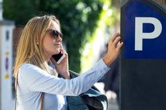 Красивая молодая женщина используя ее мобильный телефон в улице Стоковые Фотографии RF