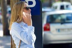 Красивая молодая женщина используя ее мобильный телефон в улице Стоковая Фотография